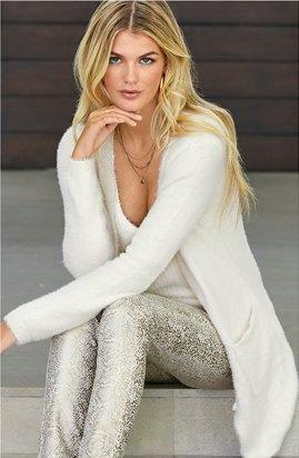 model wearing a white plush cardigan, white sweater tank top, and printed foil pants.