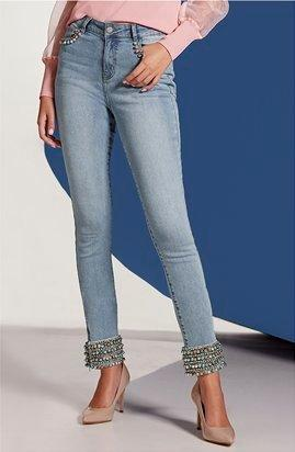 model wearing light wash ankle jeans with jewel embellishments at the cuffs.
