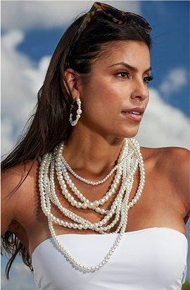 model wearing a layered pearl necklace and pearl hoop earrings.