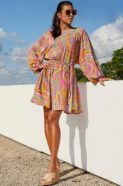 model wearing a paisley print tie-waist long sleeve dress with tan crisscross cork wedges and sunglasses.