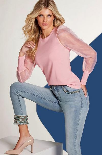 model wearing a pink illusion puff-sleeve sweater, pearl embellished light wash jeans, and tan pumps.