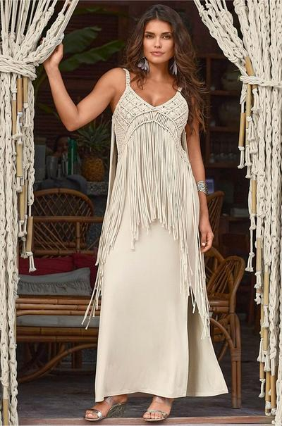 model wearing a light beige maxi dress with crochet and fringe embellishments and crystal sandals.