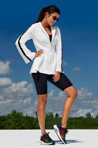 model wearing a white and black peplum bottom zip-up sports jacket, black sports bra, black biker shorts, sunglasses, and multicolored sneakers.