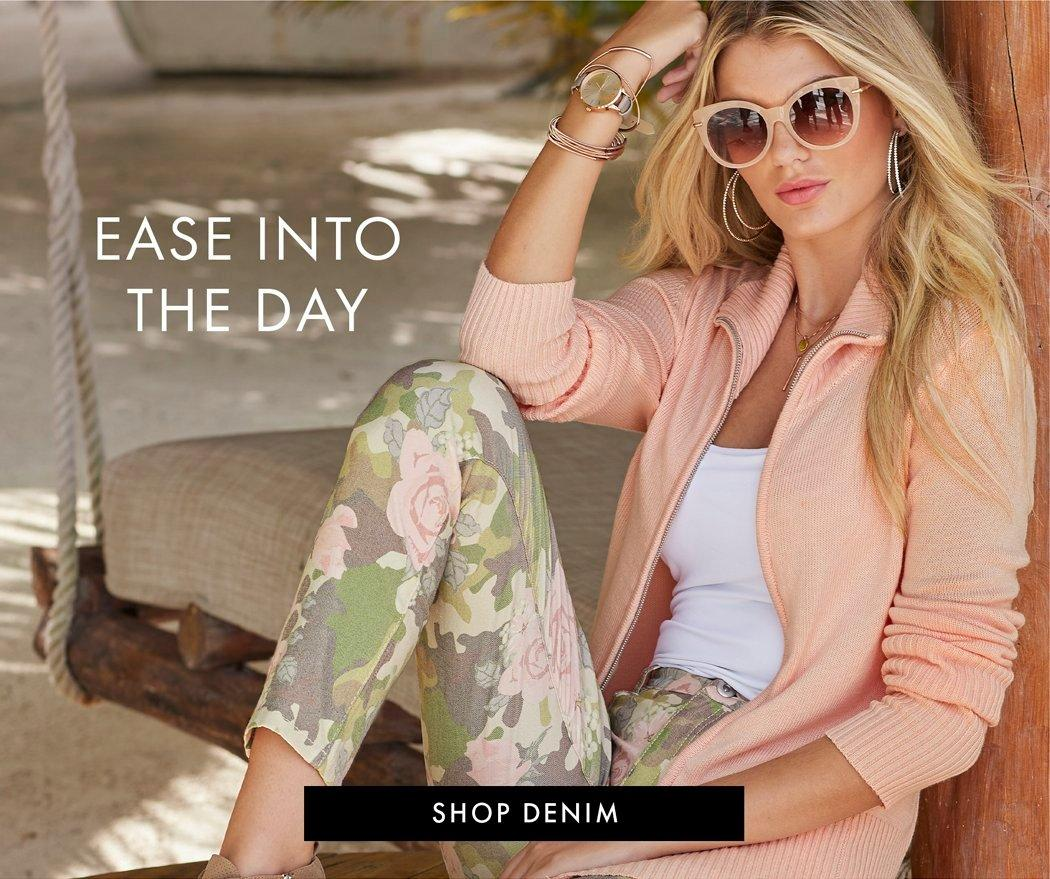 model wearing a light pink zip-up jacket, white tank top, green and pink floral pants, and pink sunglasses.