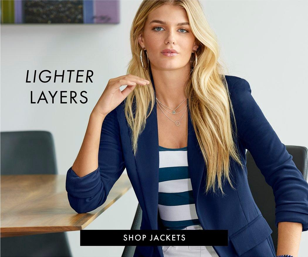 model wearing a navy blazer, white and navy striped top, white jeans, and silver hoop earrings.