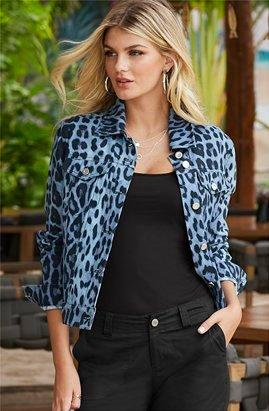model wearing a blue leopard print denim jacket, black tank top, black cargo pants, and silver hoop earrings.