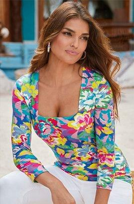 model wearing a printed multicolored three-quarter sleeve top, white jeans, and multicolored jeweled hoop earrings.