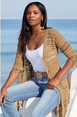 model wearing a tan crochet fringe duster, white tank top, tan jeweled belt, and light wash jeans.