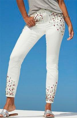 model wearing jewel embellished white jeans and silver strappy sandals.