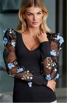 model wearing a black puff-sleeve floral embellished sweater.