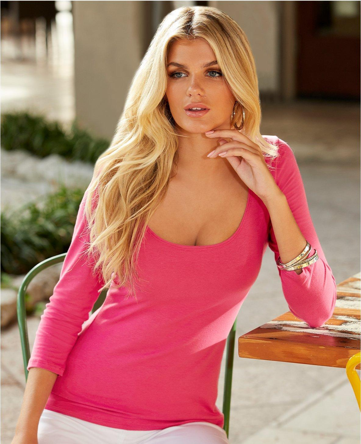 model wearing a pink three-quarter sleeve scoop neck top.