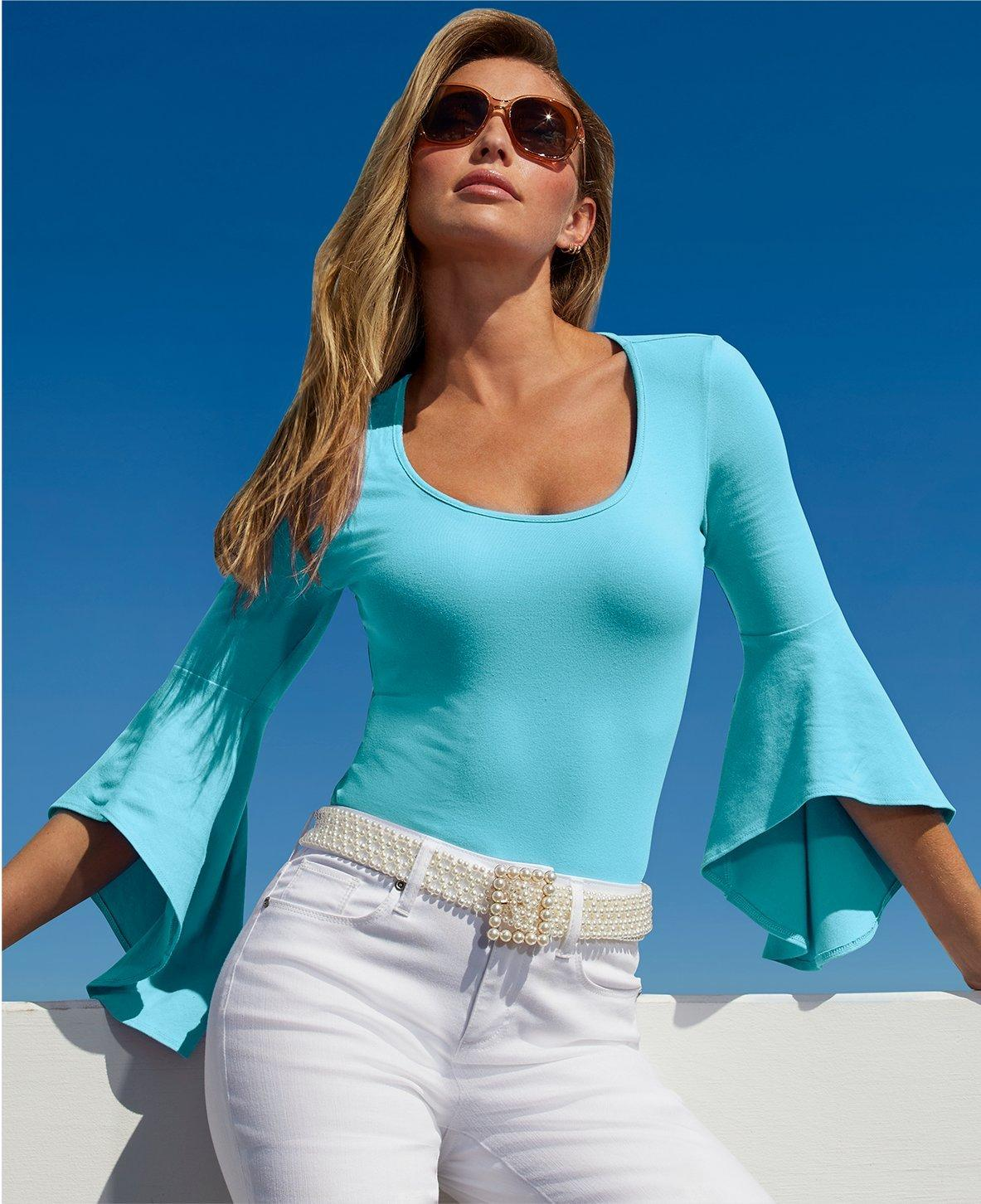model wearing a light blue flare sleeved top, pearl belt, sunglasses, and white jeans.
