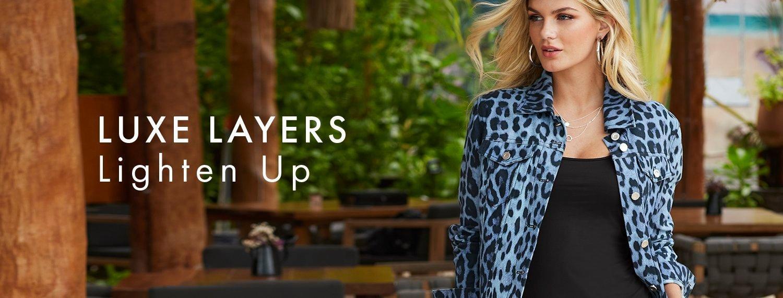 model wearing a blue leopard print denim jacket, black tank top, and silver hoop earrings.