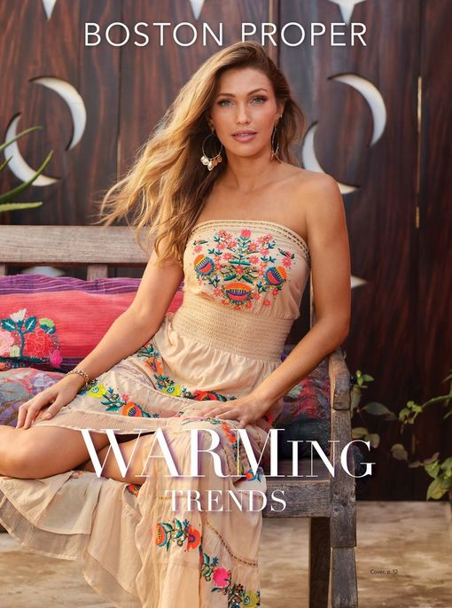 model wearing a strapless tan high-low maxi dress with bright floral embroidery.