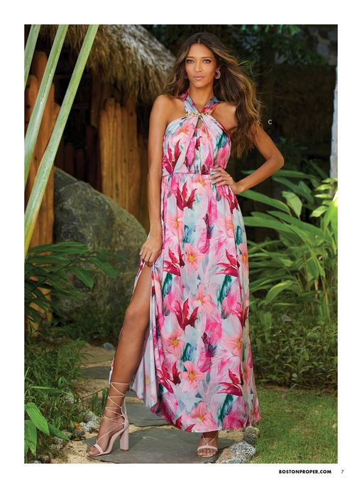 model wearing a pink and blue floral maxi dress with a halter neckline and strappy heels.