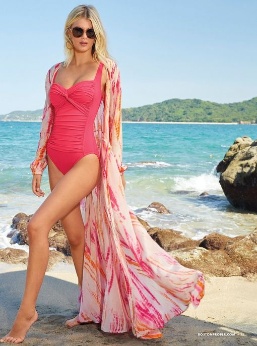 model wearing a pink one piece ruched swimsuit, pink and orange tie-dye wrap cover-up, and sunglasses.