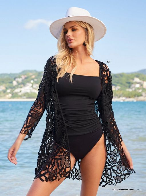 model wearing a black tankini, black lace duster, and white floppy hat.