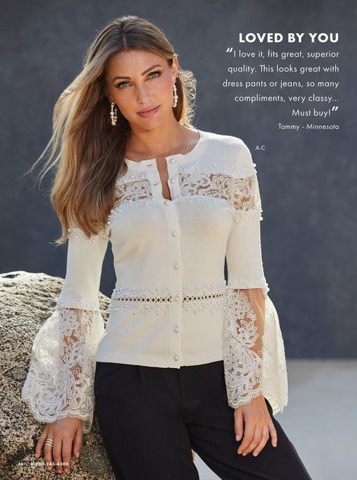 model wearing a white lace and pearl embellished flare-sleeve cardigan, black pants, and pearl hoop earrings.