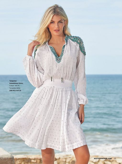 model wearing a white and turquoise embellished long sleeve dress.