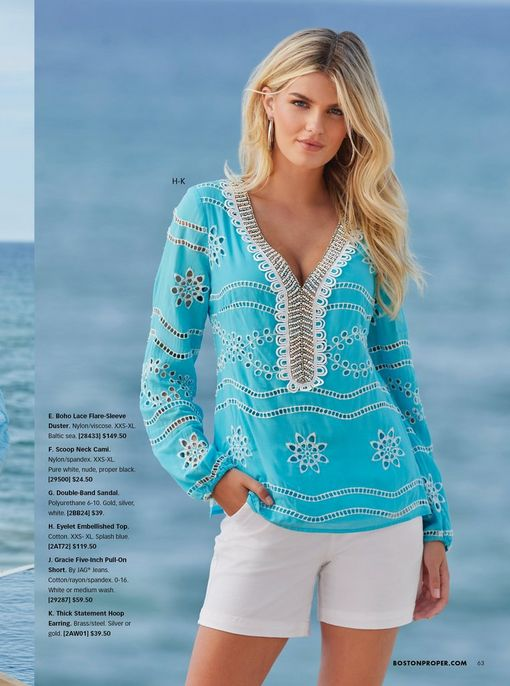 model wearing a light blue eyelet long sleeve tunic with silver embellishments and white shorts.