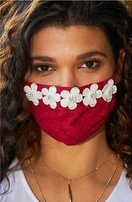 model wearing a red face mask with white flowers.