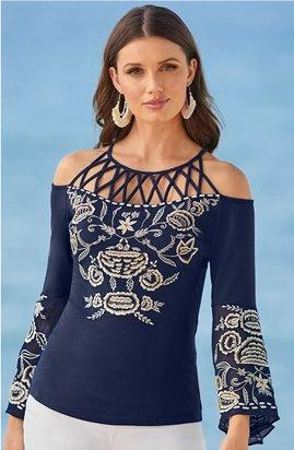 model wearing a navy cold-shoulder cage detail flare-sleeve top with white embroidery.