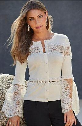 model wearing a white lace and pearl cardigan and black pants.