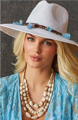 model wearing a white floppy hat with turquoise embellishments, gold layered shell necklace, and light blue lace duster.