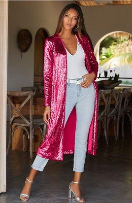 model wearing a pink sequin duster, white bodysuit, light wash jeans, white belt, and silver heels.