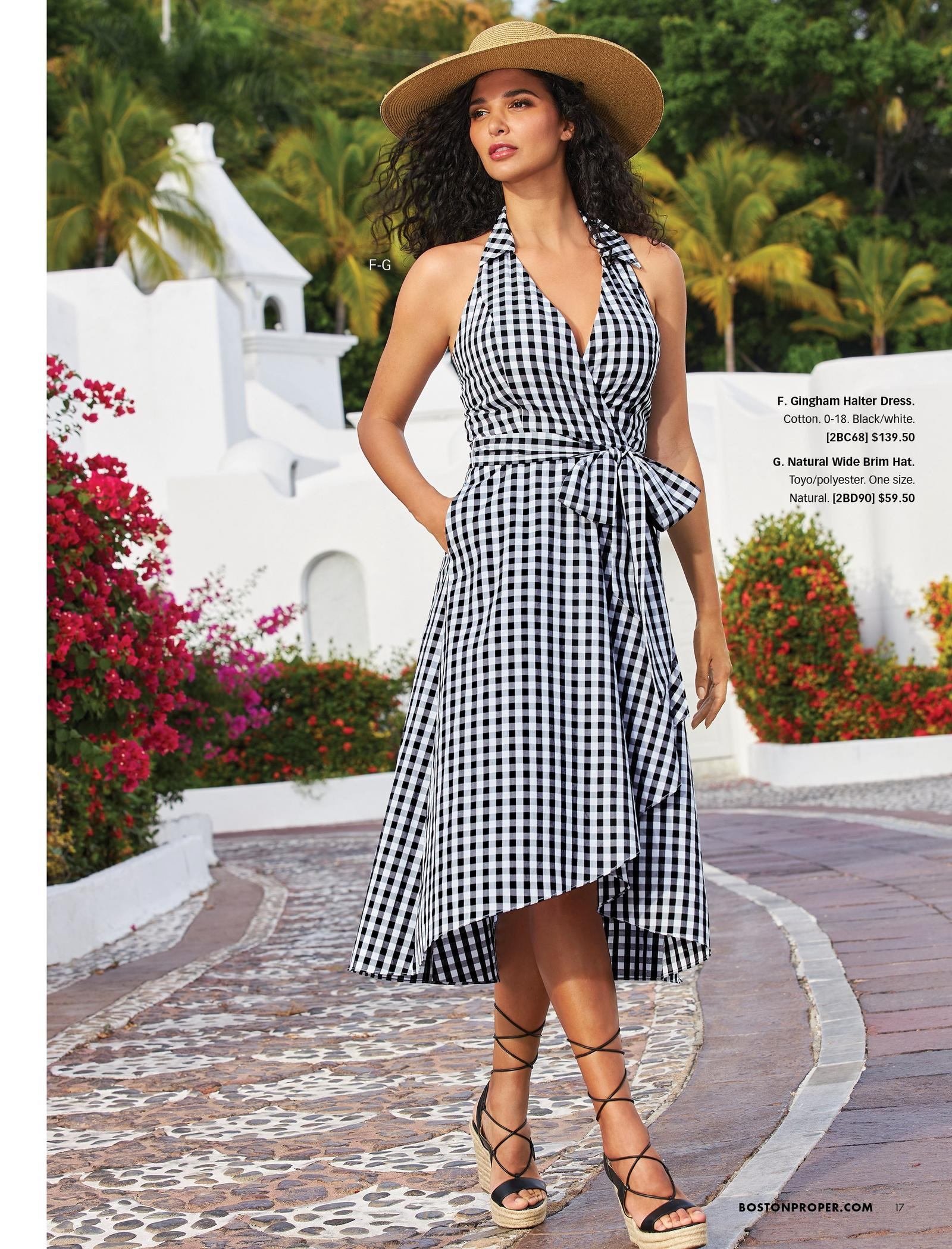 model wearing a black and white gingham halter midi dress, straw hat, and black strappy heels.