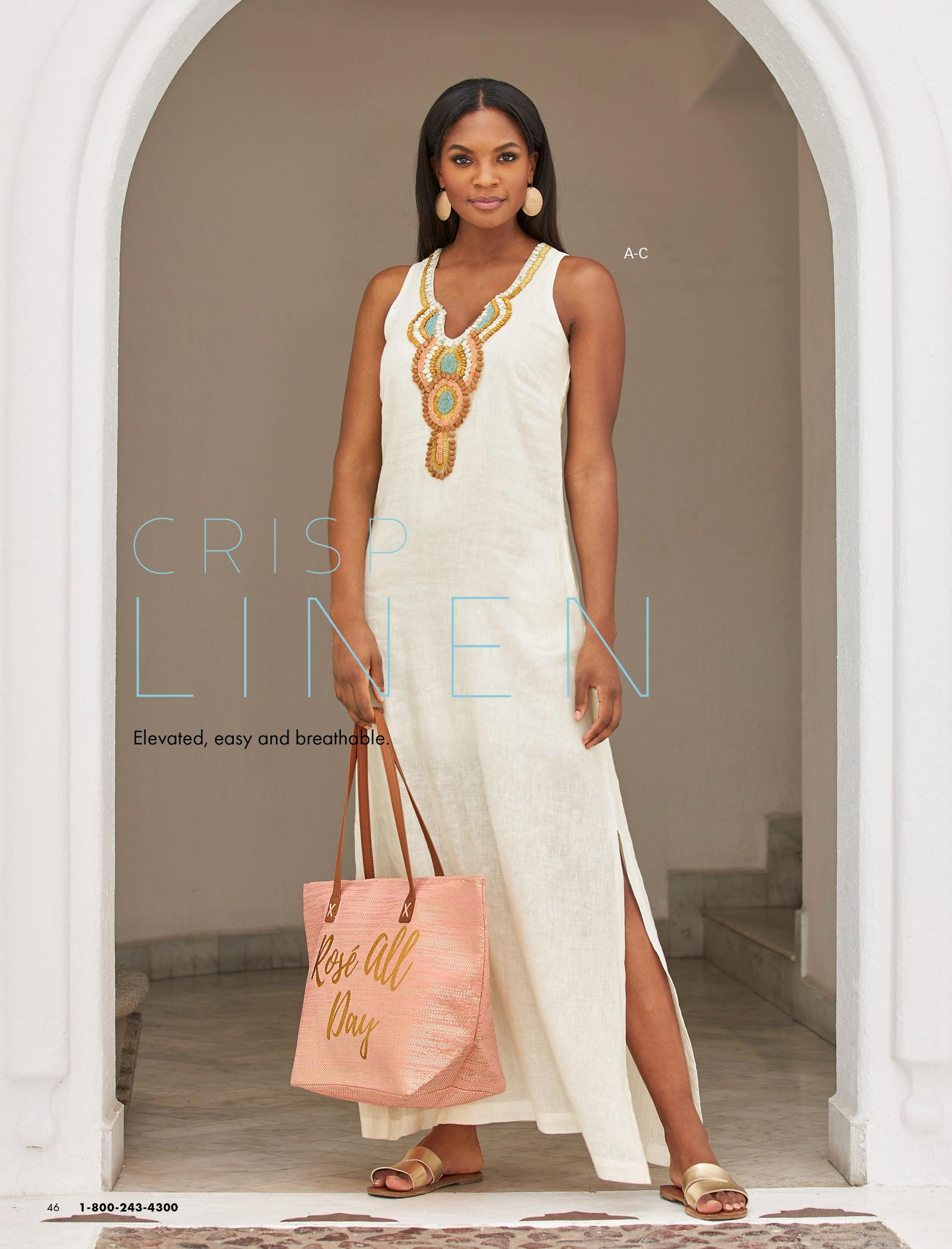 model wearing a white sleeveless linen dress with embellishments along the neckline, gold double strap sandals, gold earrings, and a pink graphic beach bag.
