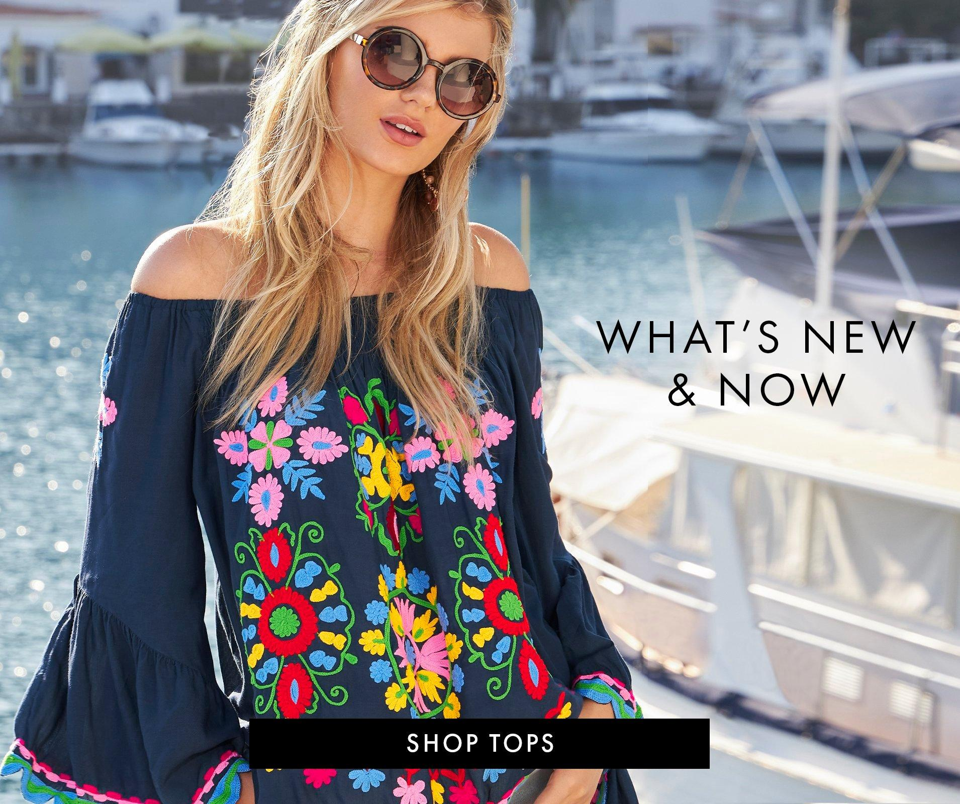 model wearing a navy off-the-shoulder flower embroidered flare-sleeve top and sunglasses.