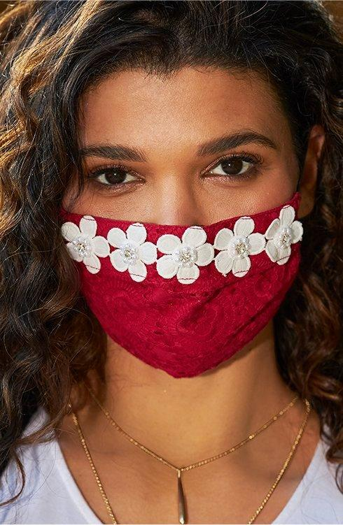 model wearing a red face mask with white daisy embellishments.
