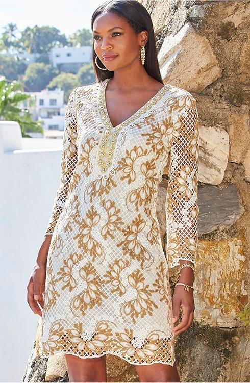 model wearing a white and gold lace long-sleeve sheath dress.