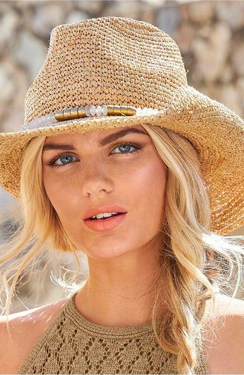 model wearing a straw hat with gold embellishments.