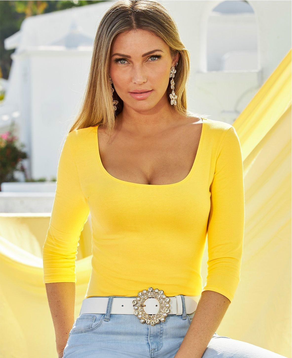 model wearing a yellow scoop neck three-quarter sleeve top, white jeweled belt, and light wash jeans.
