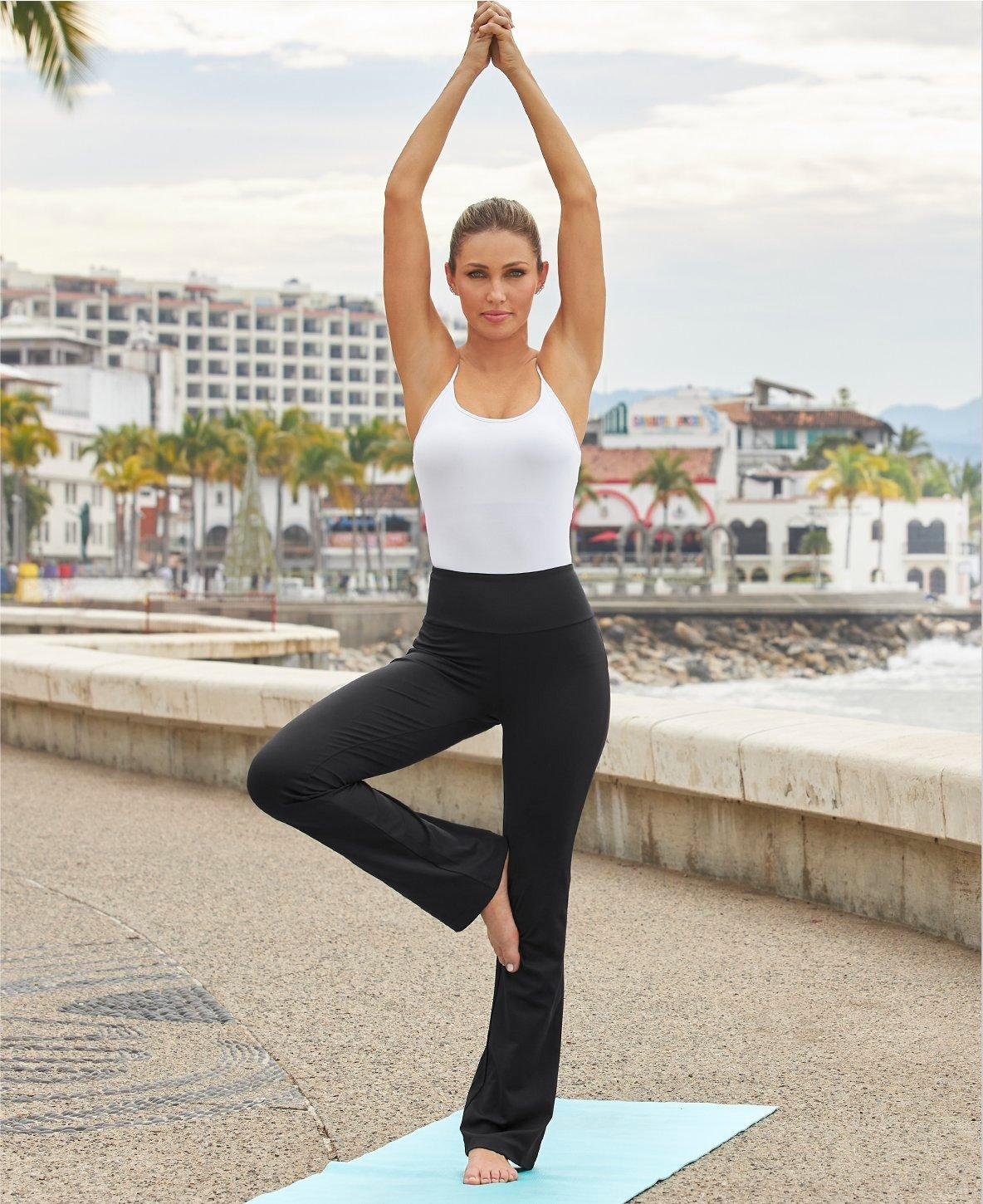 model wearing a white camisole tank top and black yoga pants.
