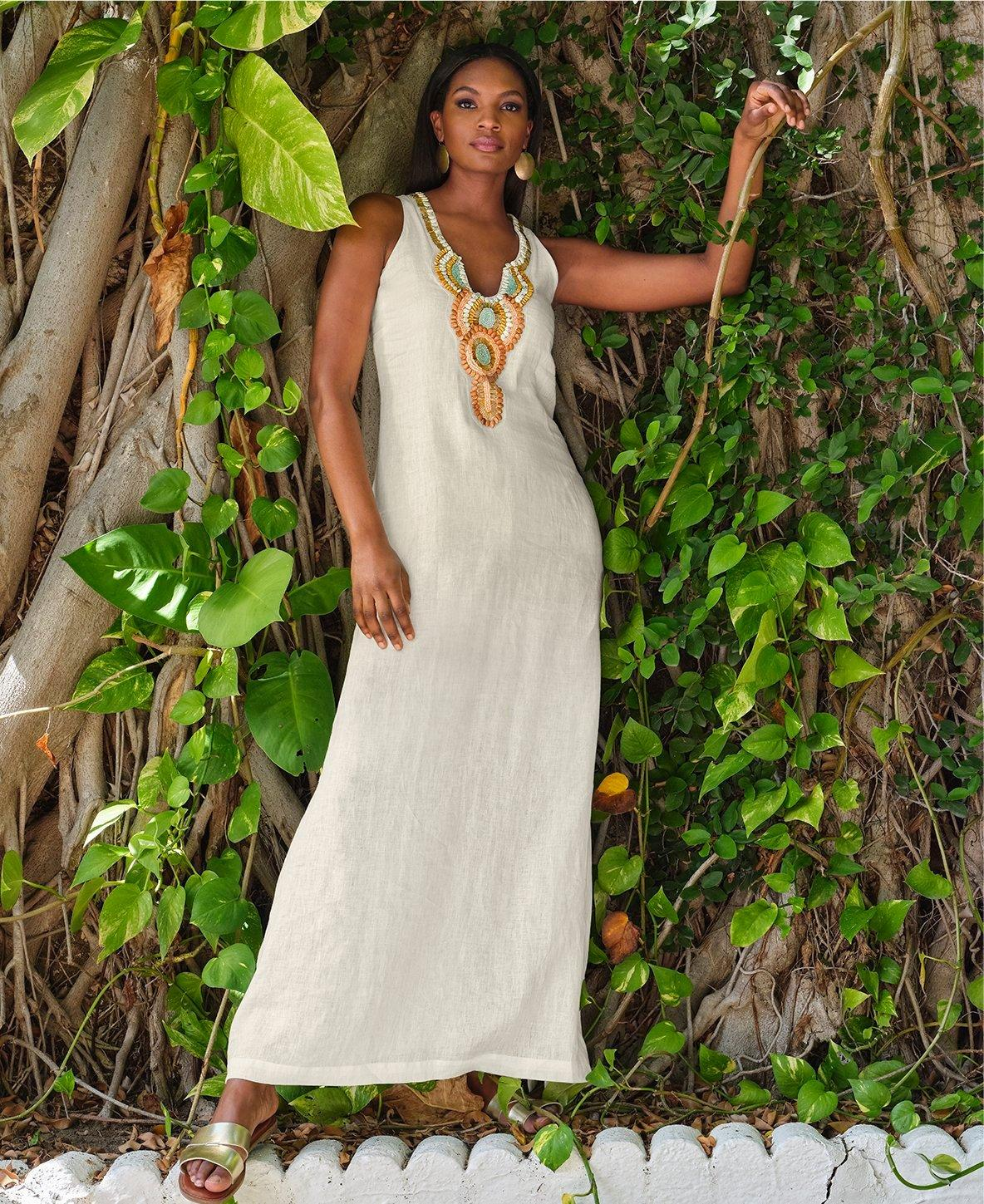 model wearing a white sleeveless maxi dress with an embellished neckline.