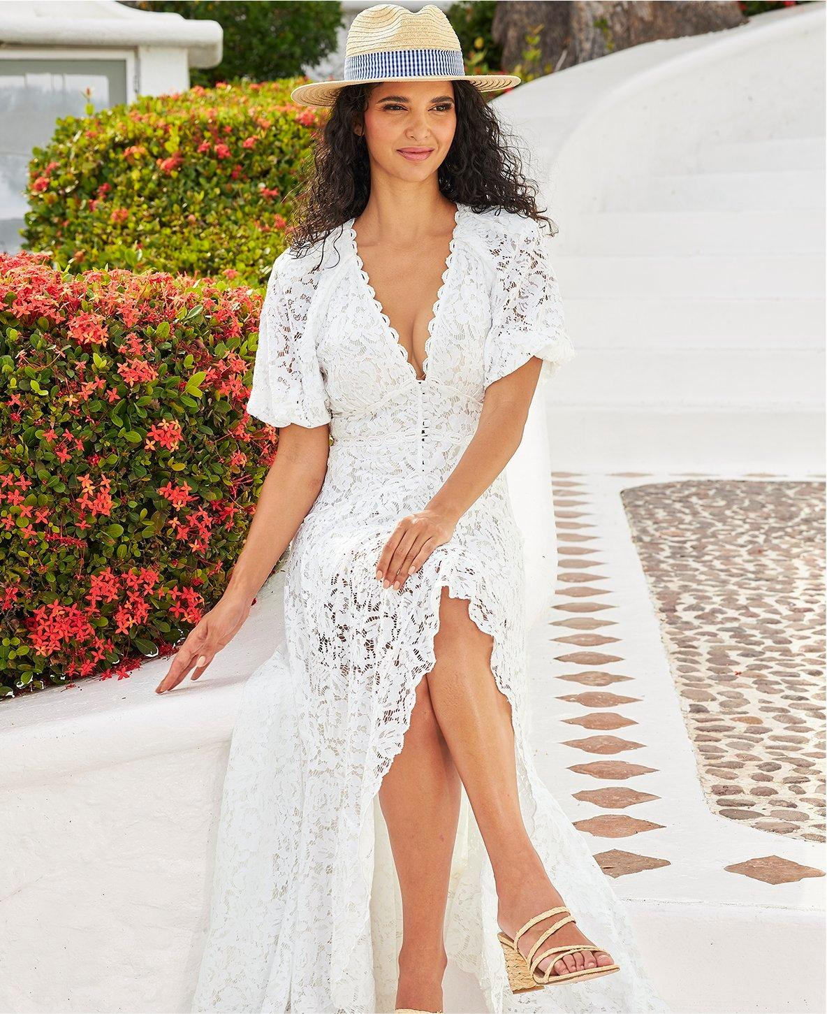 model wearing a white lace v-neck short sleeve high-low maxi dress and a straw hat with a navy gingham ribbon.