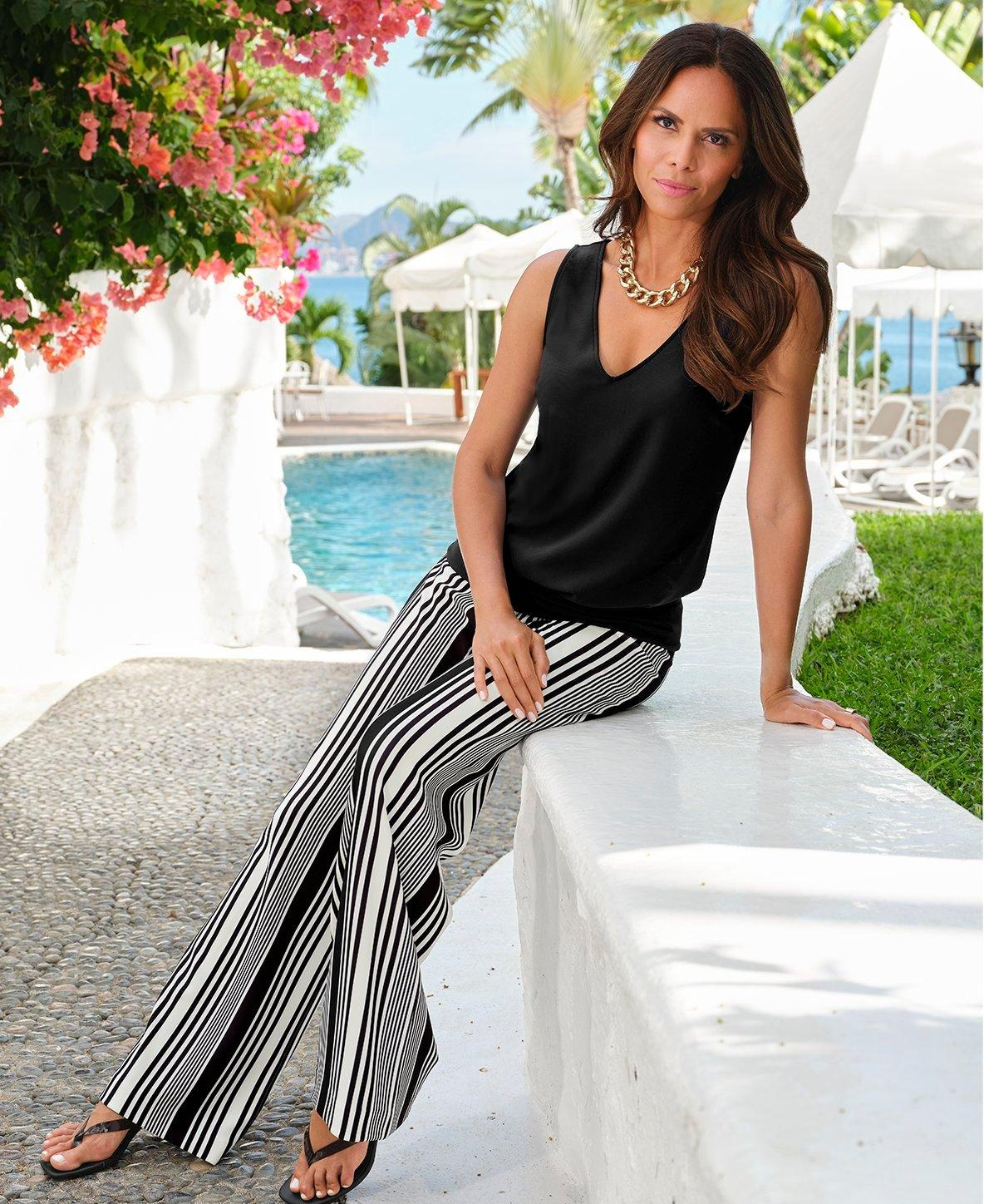 model wearing a black sleeveless blouson top, black and white striped palazzo pants, and a gold chain necklace.