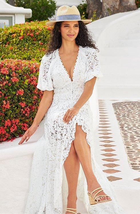 model wearing a white lace puff-sleeve high-low maxi dress and a straw hat with a gingham ribbon.