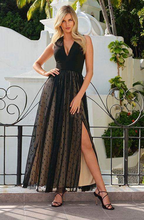 model wearing a black and nude swiss dot overlay gown dress with leg slit on model's left side.