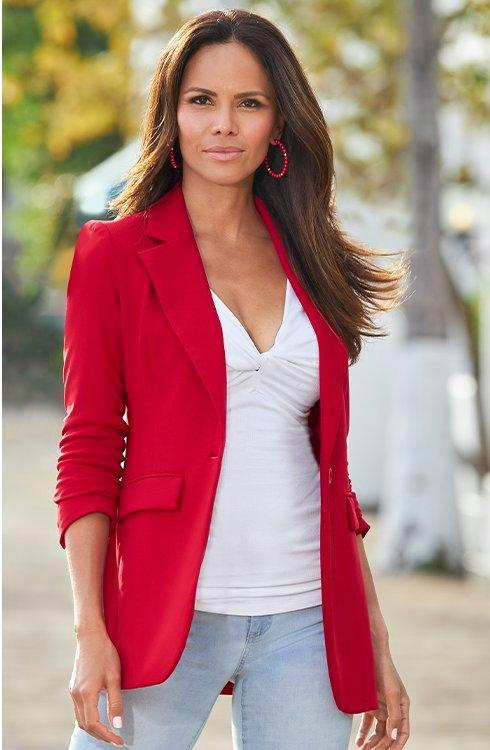 model wearing a red single breasted blazer with white knotfront top and denim jeans.