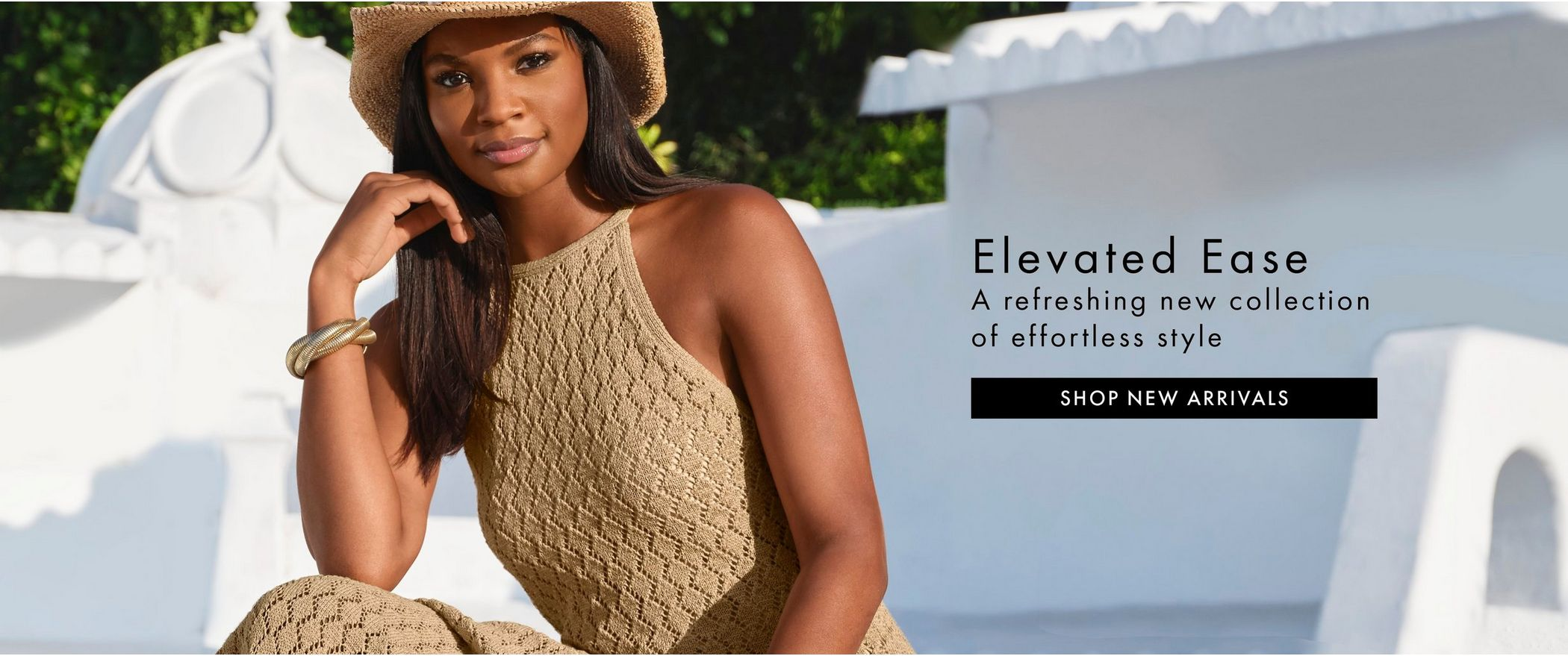 model wearing a tan crochet high neck maxi dress and a straw hat.