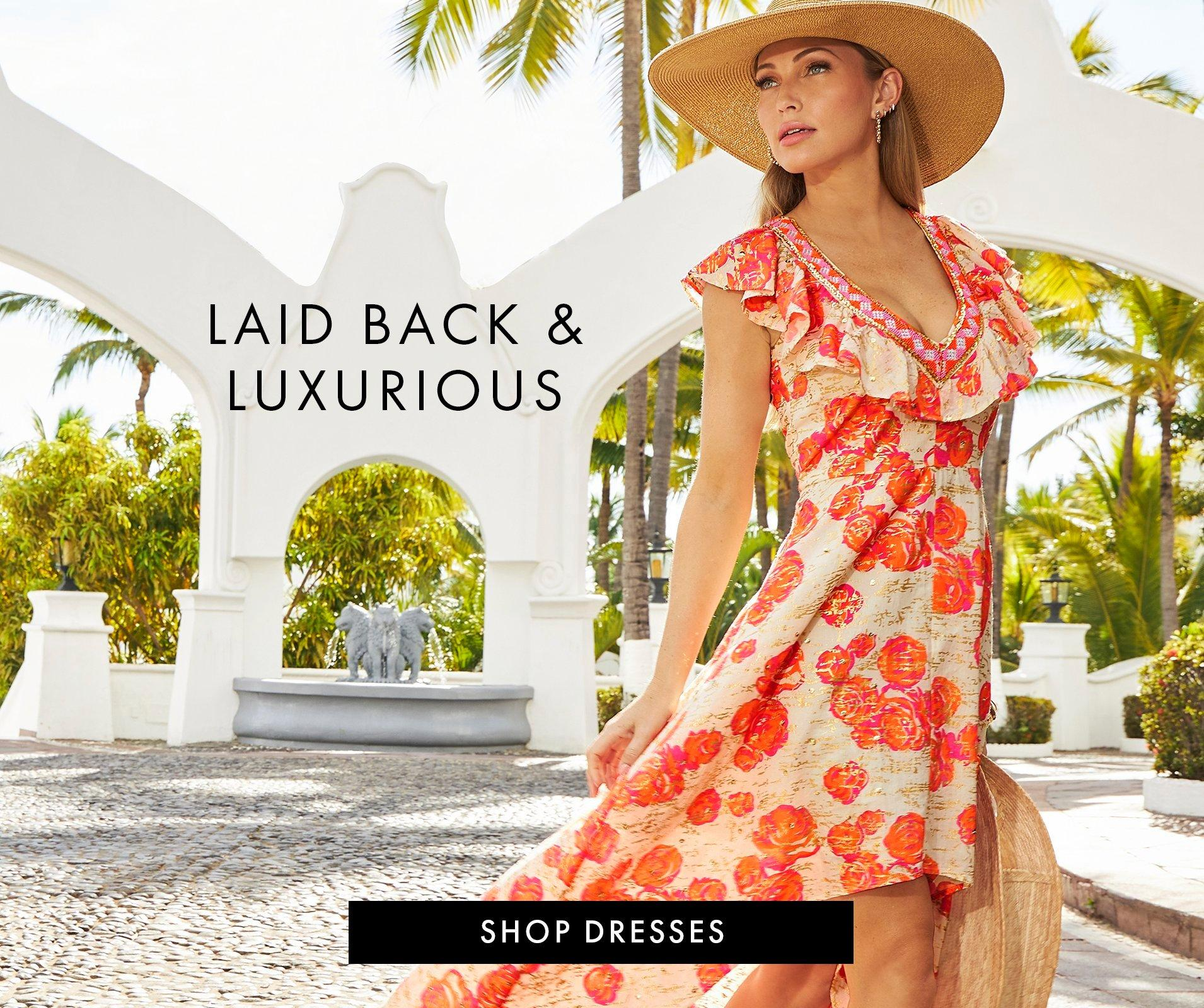 model wearing a white, orange, and red floral embroidered high-low maxi dress and straw hat.