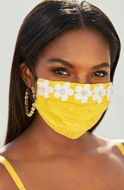 model wearing a yellow face mask with white daisy embroidery.