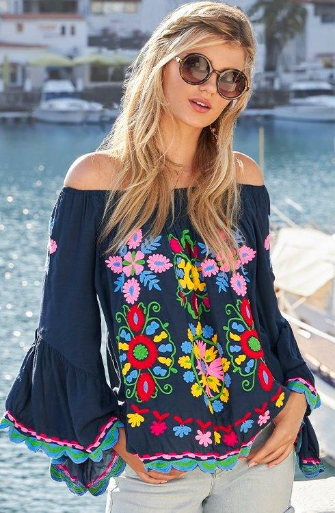 model wearing a navy blue off-the-shoulder flare sleeve embroidered top and light wash denim shorts.