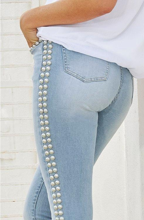 model wearing light wash jeans with silver studs along the sides.