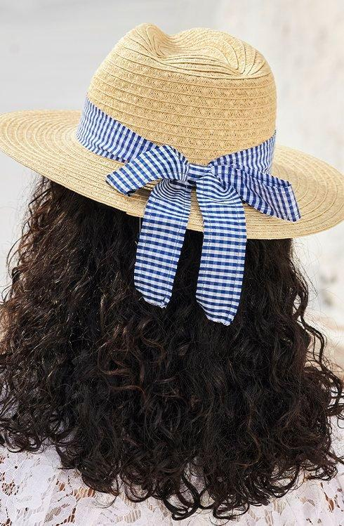 model wearing a straw hat with a navy gingham ribbon.