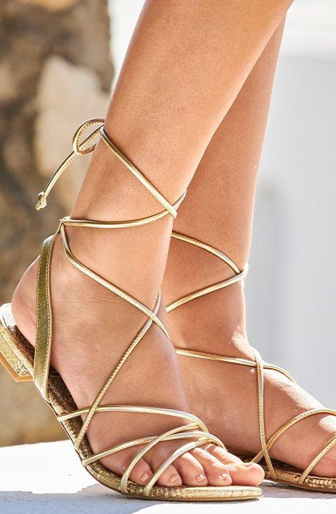 model wearing gold strappy sandals.